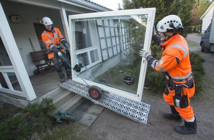 Tiivin ikkuna-asentajat siirtävät huolellisesti ikkunaa Helsinkiläiseen rivitaloyhtiöön