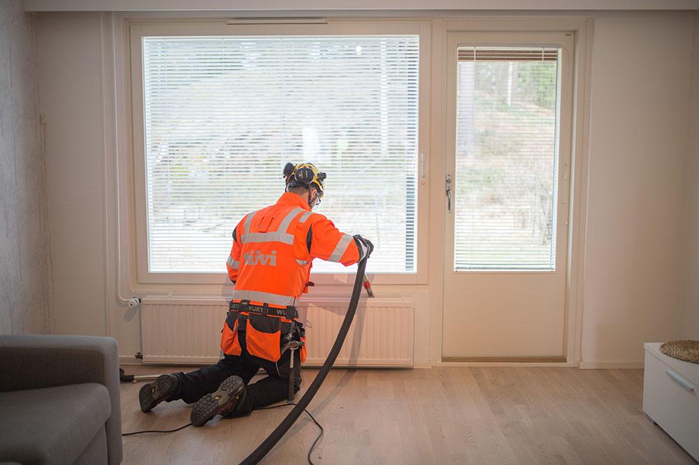 Rivitalon ikkunaremontin jälkeen Tiivin asentaja imuroi paikat puhtaaksi asennuspölystä