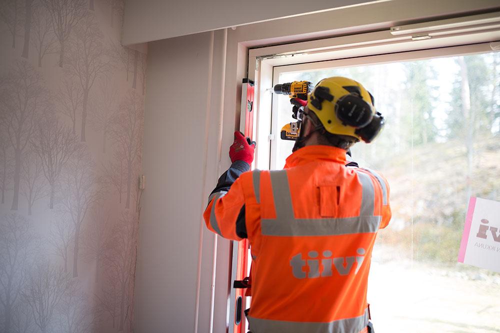 Tiivin asentaja mittaa ikkunakarmin suoruutta ja kiinnittää sen varmistamisen jälkeen paikoilleen